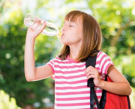 Ritratto all'aperto di ragazza felice 10-11 anni bere acqua fresca da una bottiglia. Torna al concetto di scuola. Archivio Fotografico