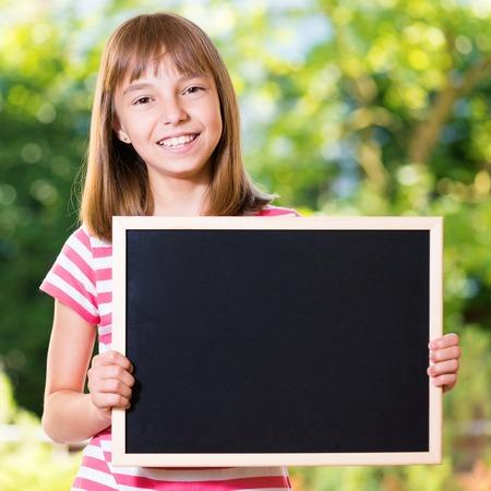 niño escuela: Retrato al aire libre de la muchacha feliz 10-11 años de edad con pequeña pizarra. Volver al concepto de escuela. Foto de archivo