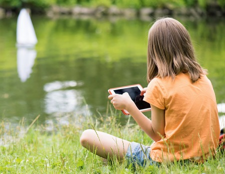 remote controlled: Girl playing with a remote controlled boat. Handmade model sailboat on lake - child is playing with tablet.