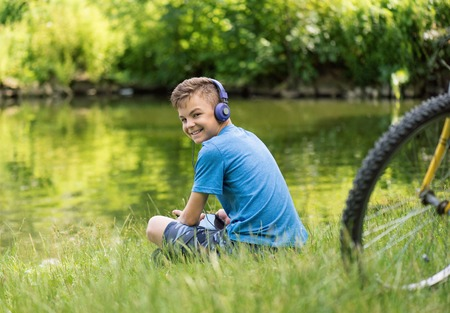 Teen boy with tablet pc and headphones listening to music or watching video in summer park at lakeside. Child resting after biking.