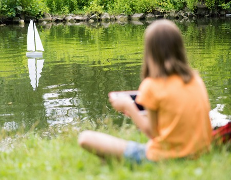 remote controlled: Girl playing with a remote controlled boat. Handmade model sailboat on lake - child is playing with tablet. Out of focus girl. Selective focus limited to boat.