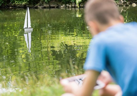 remote controlled: Teen boy playing with a remote controlled boat. Handmade model sailboat on lake - children is playing with tablet. Selective focus limited to boat.