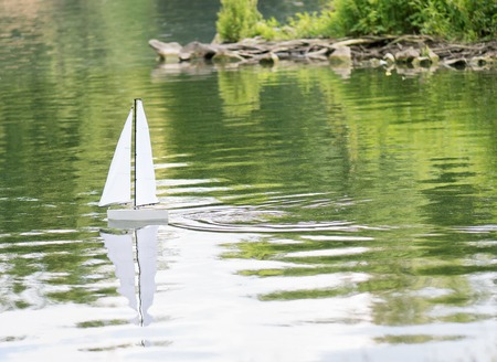 controlled: Radio controlled boat sailing on water - lake or pond in summer park