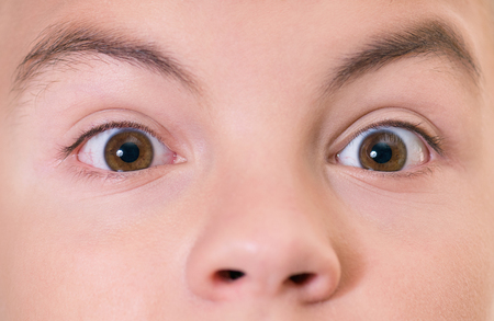 brown eyes: Close-up of shocked boy with brown eyes looking directly at the camera Stock Photo