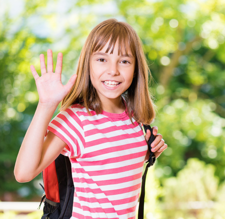 Smiling girl 10-11 year old stretching her right hand up for greeting .Beautiful schoolgirl with backpack posing outdoors.