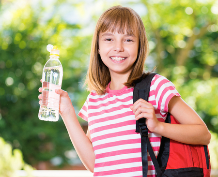 Outdoor portrait of happy girl 10-11 year old with schoolbag and bottle of fresh water. Back to school concept. Stock Photo