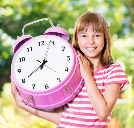 Outdoor portrait of happy girl 10-11 year old with big alarm clock. Back to school concept.