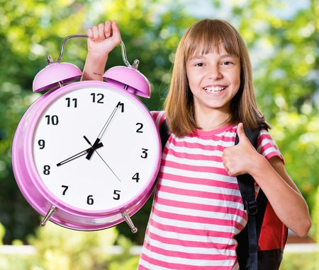 Outdoor portrait of happy girl 10-11 year old with big alarm clock and backpack. Back to school concept. Stock Photo