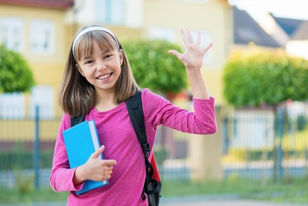 hi back: Outdoor portrait of happy child 10-11 year old with book and backpack. Girl stretching her left hand up for greeting. Back to school concept.