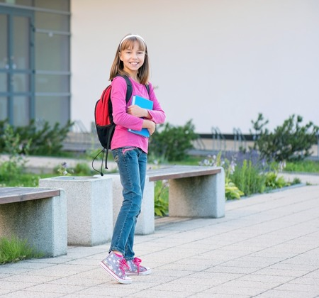 Happy girl holding books on the first school day. Full length outdoor portrait.