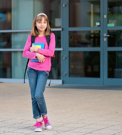 day of school: Girl with book and backpack. Child in yard on the first school day. Full length outdoor portrait.