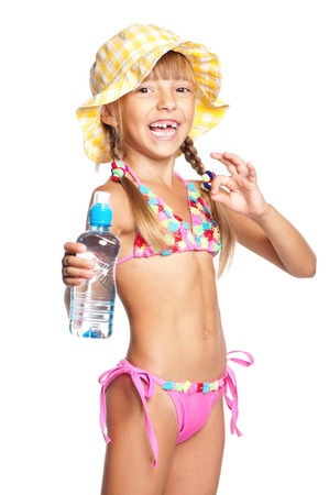 Happy little girl in swimsuit with bottle of water showing ok, isolated on white background