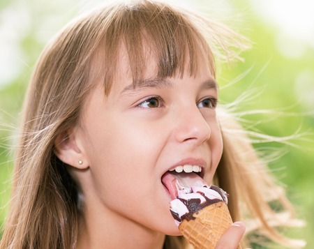 Happy girl 10-11 year old eating ice cream cone. Outdoor portrait.