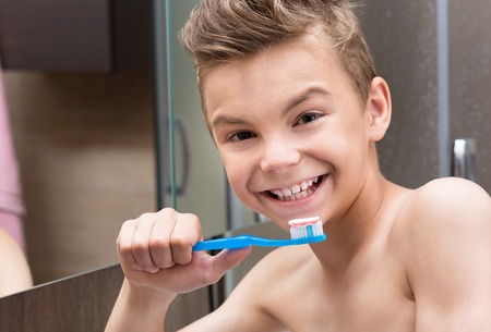 child smile: Smiling teen boy brushing teeth in bathroom Stock Photo