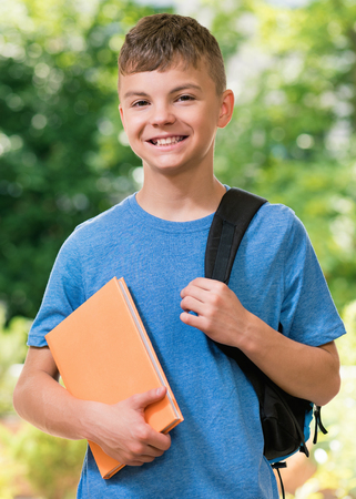 Teen boy 12-14 year old with schoolbag and book posing outdoors. Stock Photo