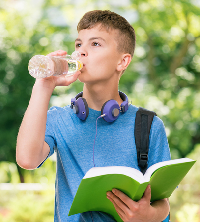 Mineral: Teen boy 12-14 year old with bottle of fresh water and book. Student teenager with headphones and schoolbag posing outdoors.