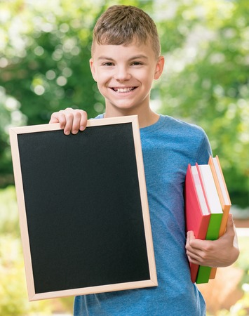 Outdoor portrait of happy teen boy 12-14 year old with small blackboard and books. Back to school concept. Stock Photo