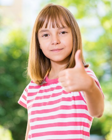 Portrait of happy girl 10-11 year old showing thumb up gesture. Beautiful schoolgirl posing outdoors.