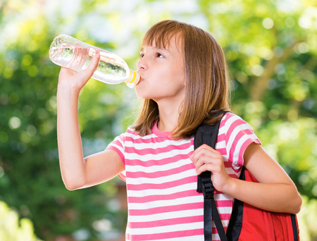 student: Outdoor portrait of happy girl 10-11 year old drinking fresh water from a bottle. Back to school concept.