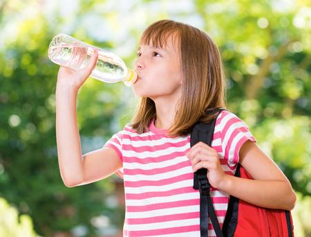 Venkovní portrét šťastné dívky 10-11 let staré pití čerstvé vody z láhve. Koncept školy.