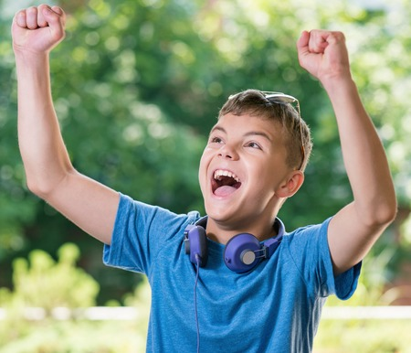 Victory screaming teen boy 12-14 year old. Winner boy with headphones and sunglasses posing outdoors. Stock Photo