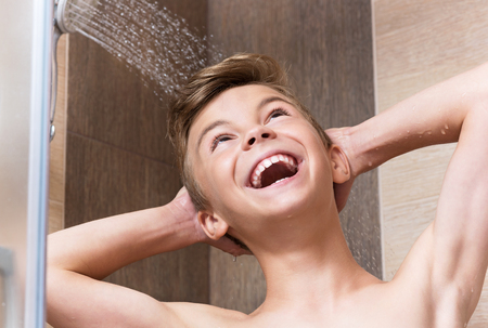 Happy teen boy bathing under a shower - washing head, in the bathroom at home