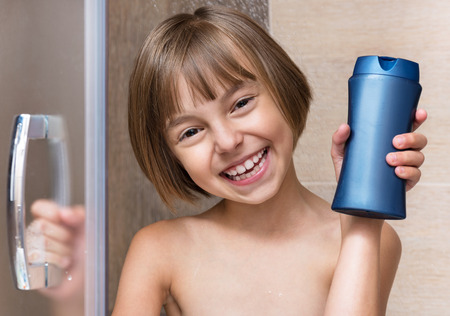showering: Smiling beautiful little girl bathing under a shower - washing head, in the bathroom at home