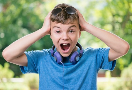 child model: Beautiful shocked teen boy with headphones and sunglasses