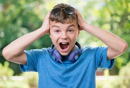 niño modelo: Hermoso muchacho adolescente sorprendida con los auriculares y las gafas de sol Foto de archivo
