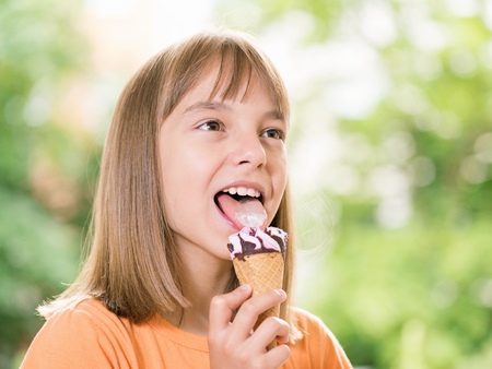 Outdoor portrait of happy girl 10-11 year old with ice cream cone