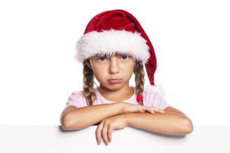 petite fille triste: Unhappy little Santa Claus. Sad Christmas little girl in red Santa hat peeking from blank board, isolated on white background. Space for text.