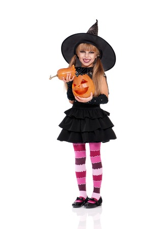 Halloween witch with a magic pumpkin - full length portrait. Happy beautiful little girl in witches hat and costume holding carved pumpkin, isolated on white background