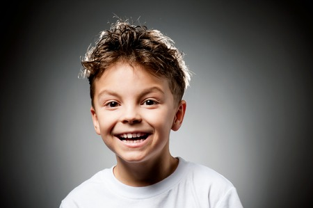 Portrait of happy child - laughing boy with smile on gray background
