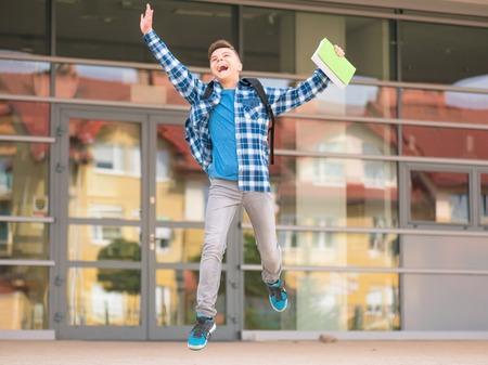 niños saliendo de la escuela: muchacho adolescente feliz con el libro y la mochila en el primer día de clases. Emocionado por volver a la escuela después de las vacaciones. Retrato de cuerpo entero al aire libre. Foto de archivo