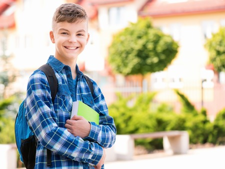 Outdoor portrait of happy teen boy 12-14 years old with books and backpack. Young student beginning of class after vacation. Back to school concept. Stock Photo