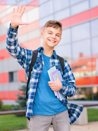 Outdoor portrait of happy child 12-14 years old with book and backpack. Boy stretching his left hand up for greeting. Back to school concept.