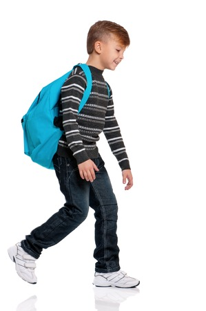 Full length portrait of a smiling schoolboy with backpack on the first school day. Boy going isolated on white background. Back to school after vacation.