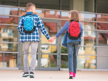 niños saliendo de la escuela: Happy children - boy and girl with books and backpacks on the first school day. Young students beginning of class after vacation. Full length outdoor portrait in yard.