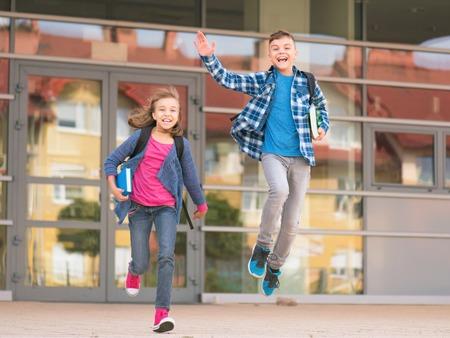 niños saliendo de la escuela: Niños felices - niño y niña con libros y mochilas en el primer día de clases. Emocionado por volver a la escuela después de las vacaciones. Retrato de cuerpo entero al aire libre. Foto de archivo
