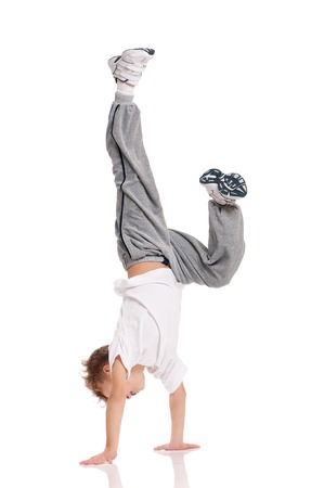 the acrobatics: Feliz ni�o acrobacia gimn�stica equilibrio postura aislada en el fondo blanco