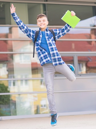 Happy teen boy with book and backpack on the first school day. Excited to be back to school after vacation. Full length outdoor portrait. Stock Photo