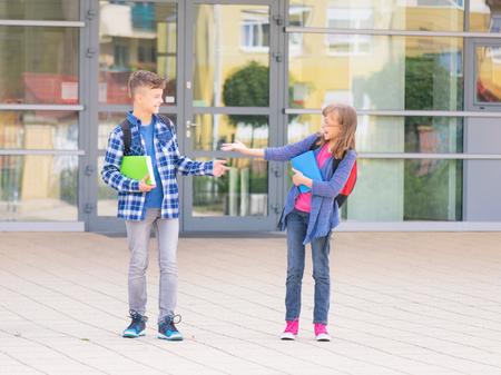 Niños felices - niño y niña con libros y mochilas en el primer día de clases. Los jóvenes estudiantes comienzo de la clase después de las vacaciones. Retrato de longitud completa al aire libre en el patio.