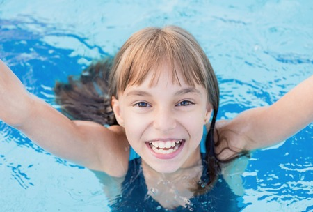 enjoyable: Close-up portrait of happy girl in the swimming pool at aquapark. Cute child having fun enjoyable time on vacation. Looking at camera.