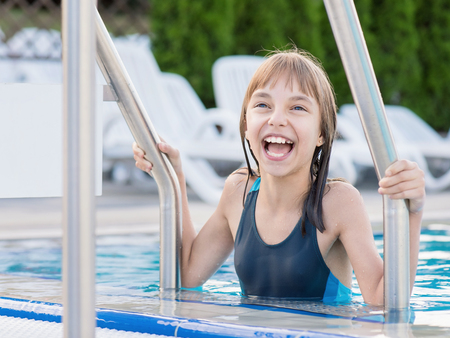 Close-up portrait of happy girl in the swimming pool at aquapark. Cute child having fun enjoyable time on vacation. Kid exiting the pool.