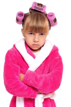 hair curlers: Adorable little girl with in pink bathrobe and hair curlers playing angry wife. Child posing with folded arms, isolated on white background. Stock Photo