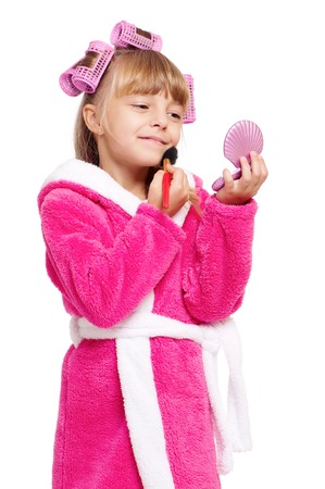 red bathrobe: Adorable little girl playing with mommys make up. Fashion little child applying make-up, isolated on white background. Kid learning to be a modern woman.