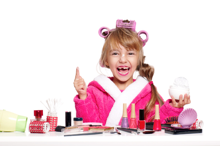 Adorable little girl playing with mommys make up. Fashion little child applying cream for face, isolated on white background. Kid learning to be a modern woman.