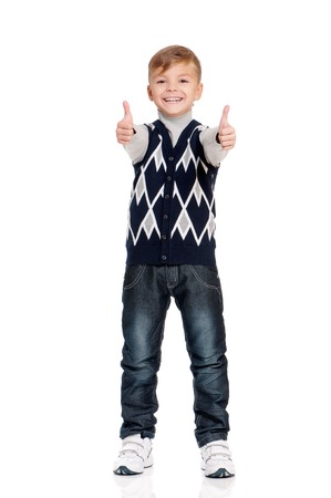 full height: Cute teenager boy standing and showing thumb up sign. Smiling school boy isolated on white background. Full height portrait happy child. Stock Photo