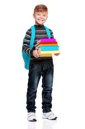 MOCHILA: muchacho adolescente linda con el morral y los libros. Colegial sonriente aislados sobre fondo blanco. retrato de altura completa niño feliz. De vuelta a la escuela.