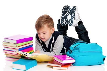 full height: Cute teenager boy with backpack and books. Smiling schoolboy isolated on white background. Full height portrait happy child lying on floor. Back to school.